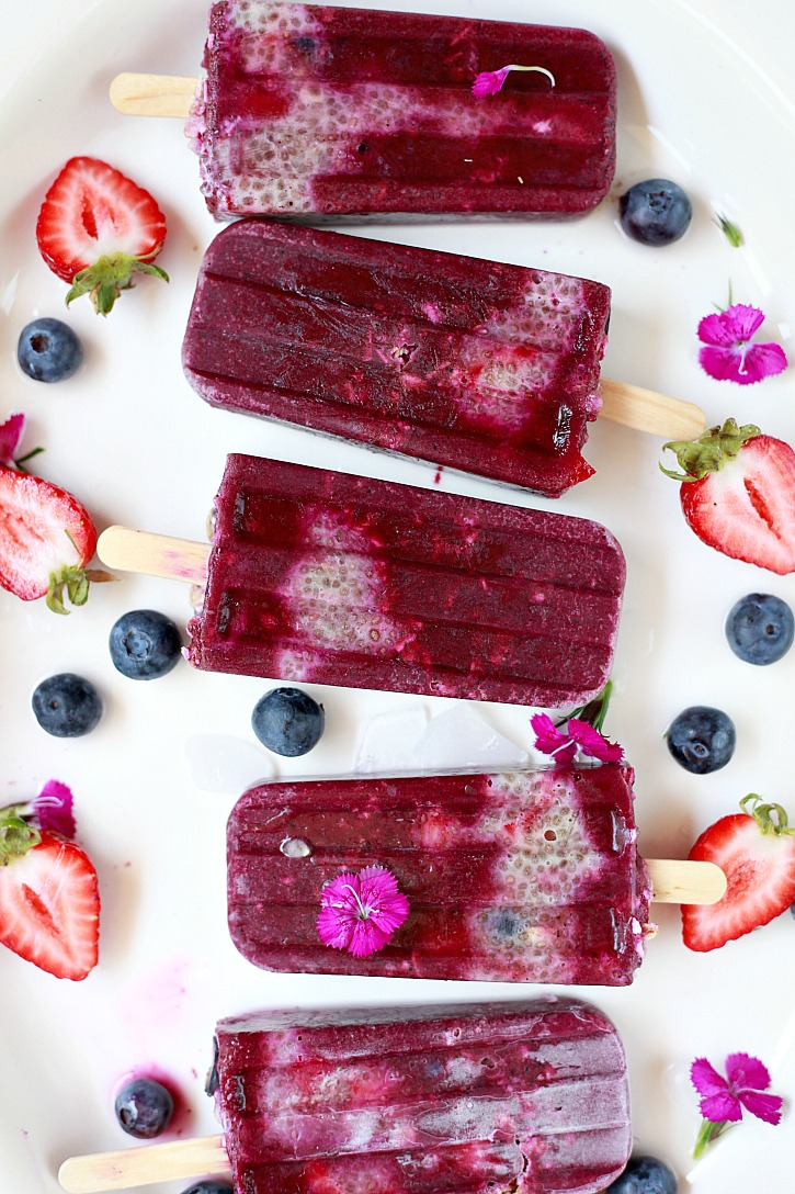 A platter of acai, chia, and granola breakfast popsicles with edible flowers and berries.