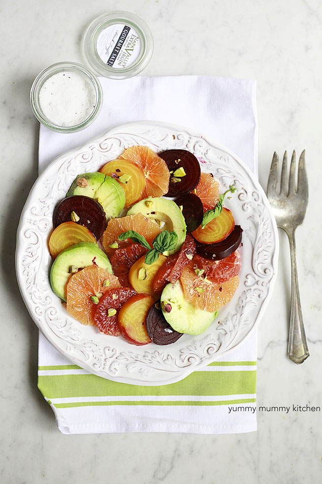 A plate with colorful citrus, roasted beets, and avocado slices.
