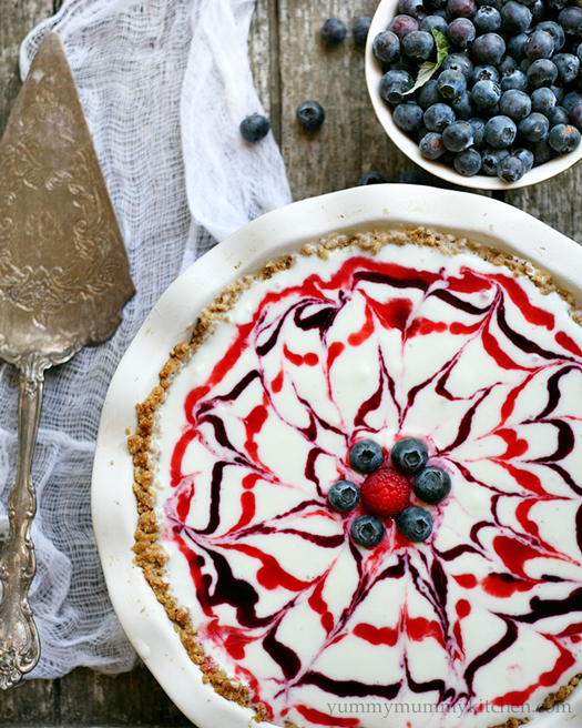 A beautiful red, white, and blue swirled ice cream pie in a granola crust made with berry sauces.