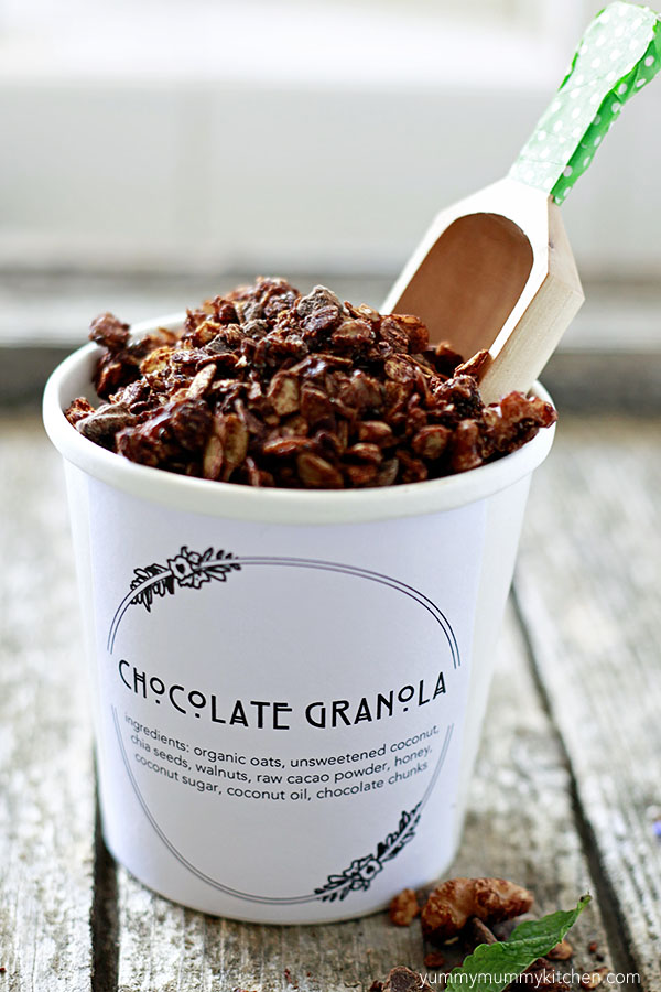 Healthy homemade chocolate granola in a container with a small wooden scoop. This granola looks like an adorable DIY edible gift idea.