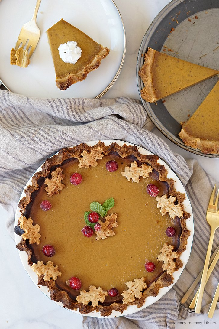This beautiful vegan and gluten free pumpkin pie is topped with sugared cranberries and pie crust leaves.