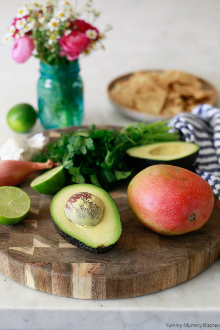 Beautiful ingredients for an easy mango avocado salsa include fresh lime juice, shallot, mango, and avocado.
