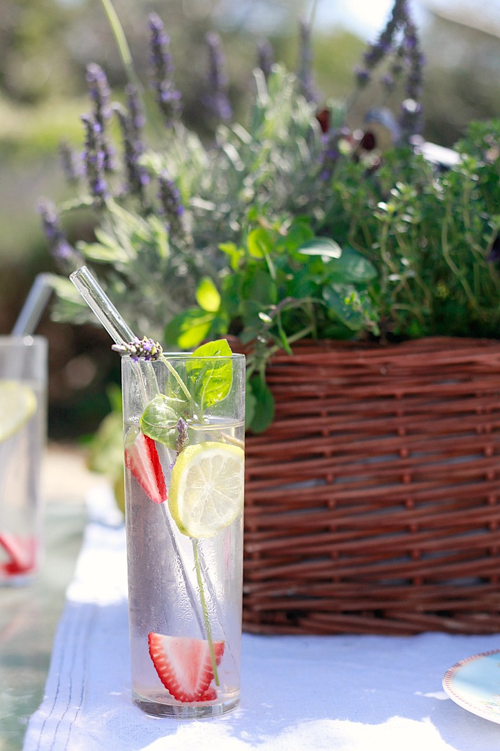 Beautiful water with fresh herbs, strawberries, and lavender form a kitchen herb garden centerpiece.