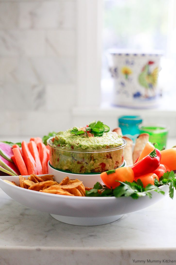 Homemade salsa guacamole in guacamole party platter with chips and vegetables makes an easy and beautiful appetizer.