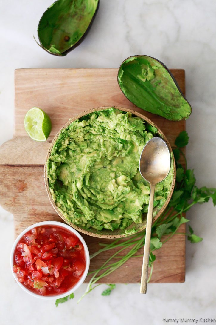 Easy guacamole being made with fresh avocados mashed in a bowl, fresh lime juice, and pre-made salsa.