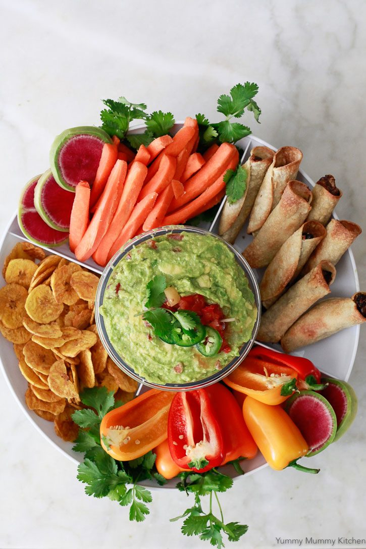 This easy salsa guacamole recipe is perfect for a beautiful guacamole platter with veggies, chips, and taquitos.