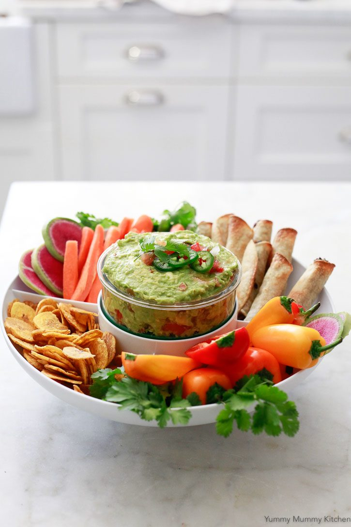 A beautiful platter with homemade salsa guacamole served in a Guac-Lock with taquitos, peppers, chips, and carrot sticks.