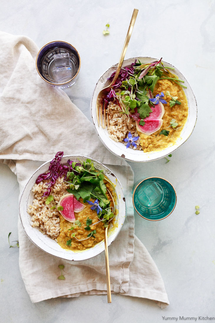 Two bowls of red lentil masoor dal with brown rice, watermelon radish, and cilantro.