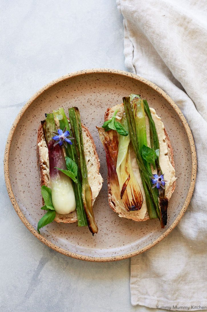 Grilled spring onions on toast with hummus, basil, and edible borage flowers.