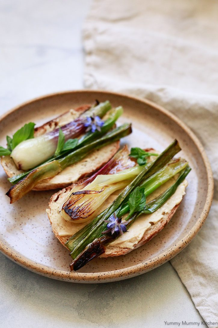 A plate with two pieces of toast topped with hummus, grilled spring onions, and fresh basil for an easy vegan spring lunch or snack.