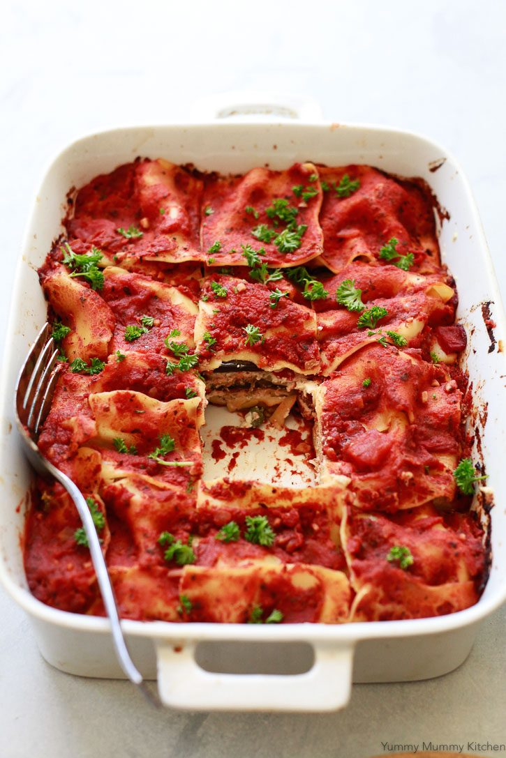 A baked vegan vegetable lasagna with eggplant in a casserole dish.