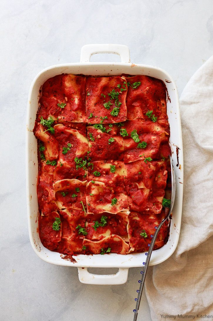 A white casserole dish of vegan lasagna cut into squares and topped with fresh parsley is ready to be served.