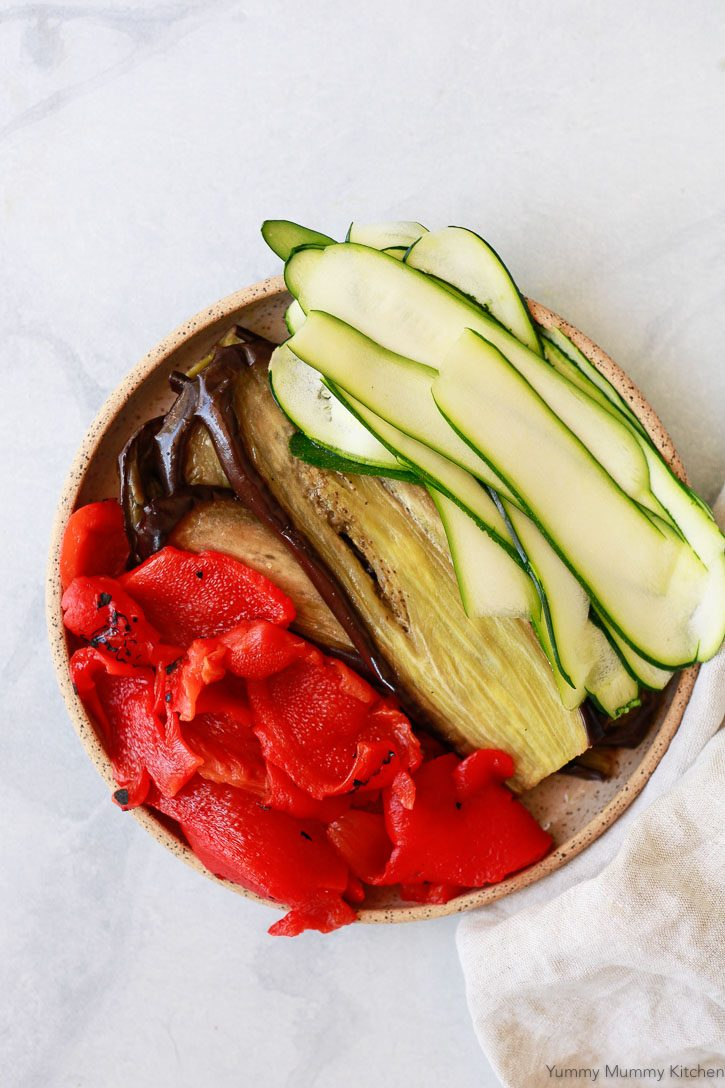 A beautiful plate of roasted red peppers, roasted eggplant slices, and sliced zucchini ready to layer in a vegetarian vegan lasagna.
