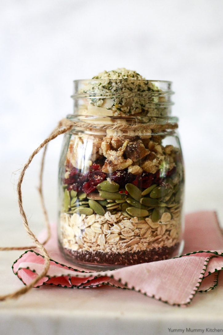 A jar layered with superfood muesli made with oats, chia seeds, pumpkin seeds, cranberries, walnuts, and hemp sees.