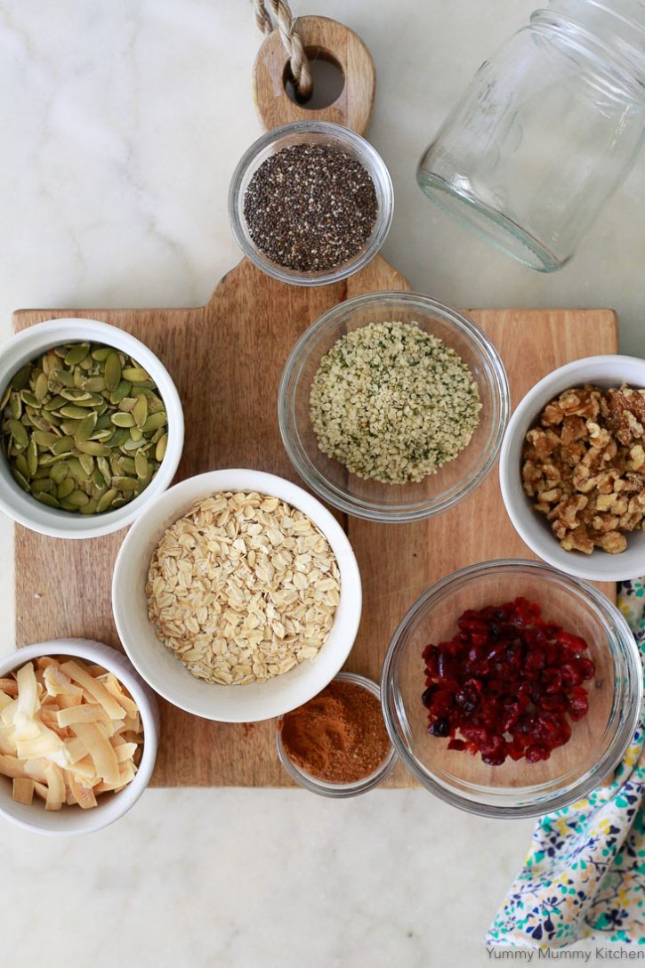 Homemade bircher muesli ingredients on a cutting board including oats, seeds, dried fruit, cinnamon, and coconut sugar.