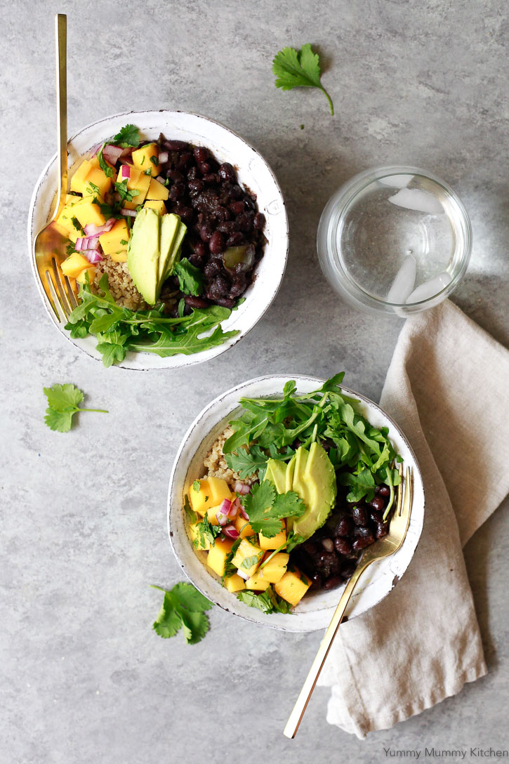 Two white bowls filled with rice, Cuban black beans, mango salsa, arugula, and avocado with gold forks.