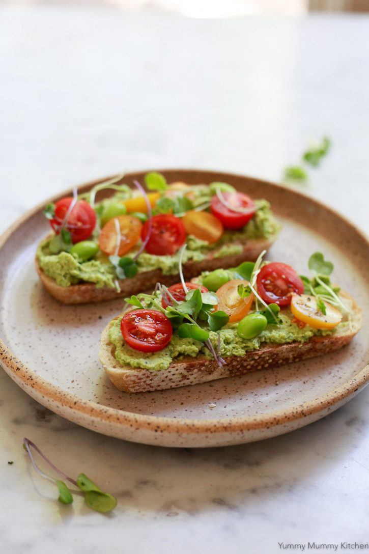 This healthy vegan edamame basil hummus recipe is perfect on sourdough toast with cherry tomatoes and microgreens for a plant based lunch.