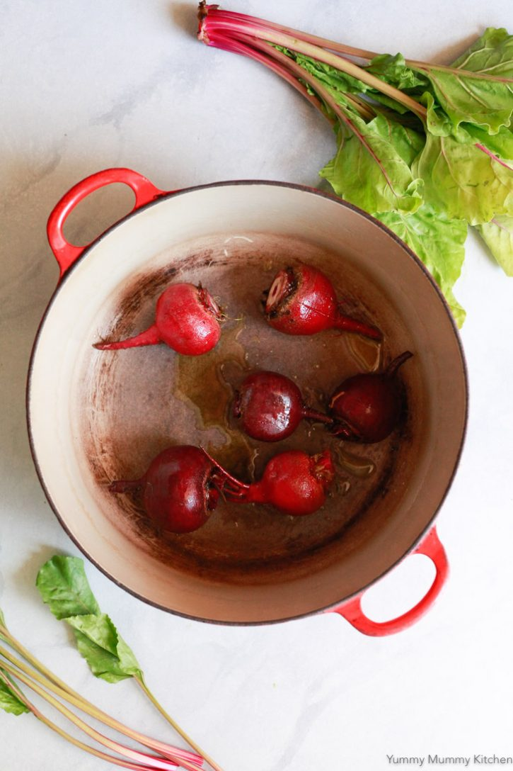 Beet roots in a Dutch oven are drizzled with olive oil before getting roasted in the oven without foil.