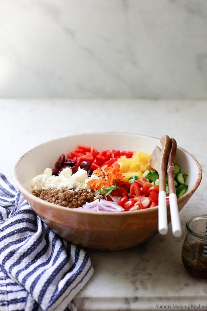 Cold vegan lentil salad with colorful Greek inspired ingredients in a wooden salad bowl.