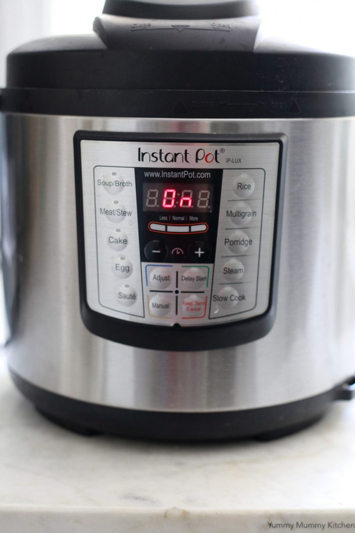 An Instant Pot Pressure Cooker on a white counter.