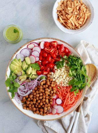 A big beautiful Southwestern salad with corn, roasted chickpeas, tomatoes, romaine, and avocado dressing.