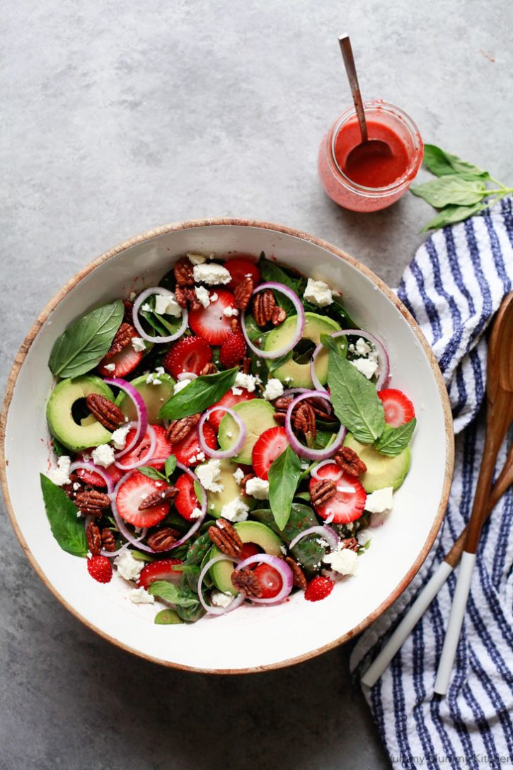Strawberry spinach salad with red onions, pecans, strawberries, avocado and feta in a white salad bowl. This beautiful salad is dressed with a homemade strawberry balsamic vinaigrette.