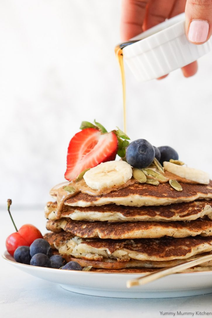 Syrup pouring over a stack of vegan banana pancakes with fresh berries, banana, almond butter, and pepitas.