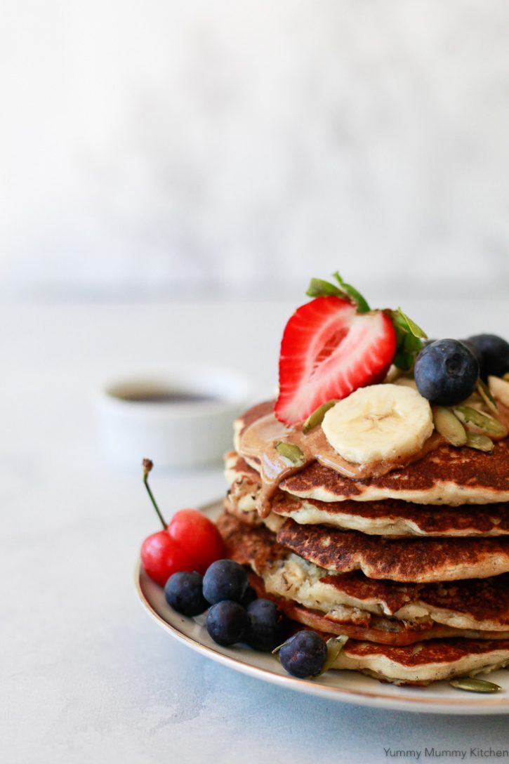 A close-up photo of vegan banana pancakes, blueberries, strawberries, and pepitas with almond butter dripping down the side. These vegan banana pancakes are and easy one-bowl vegan breakfast.