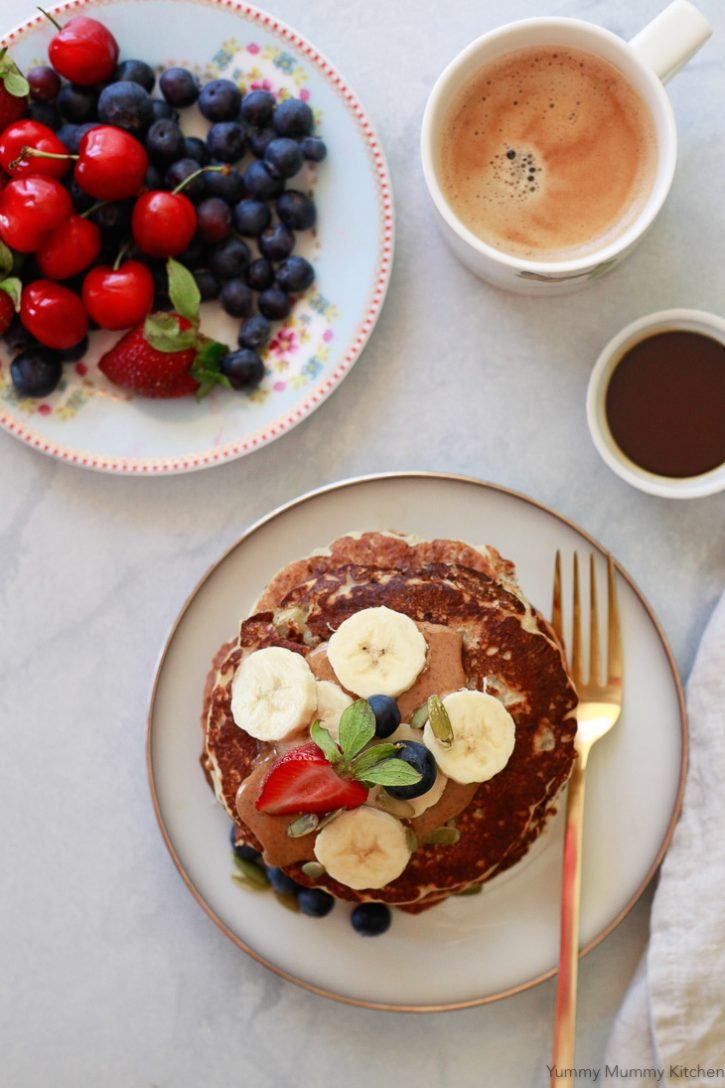 A stack of vegan banana pancakes topped with berries and almond butter served with fresh blueberries and cherries, a cup of syrup, and coffee. This beautiful vegan breakfast is perfect for Mother's Day or any day!
