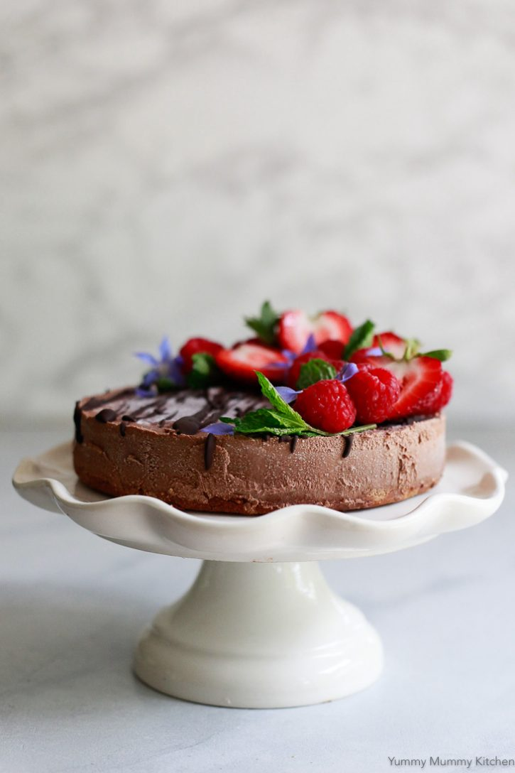 This beautiful vegan chocolate cheesecake is on a cake stand and topped with raspberries, strawberries, mint, and edible borage flowers. It's dairy-free, paleo, and gluten-free.