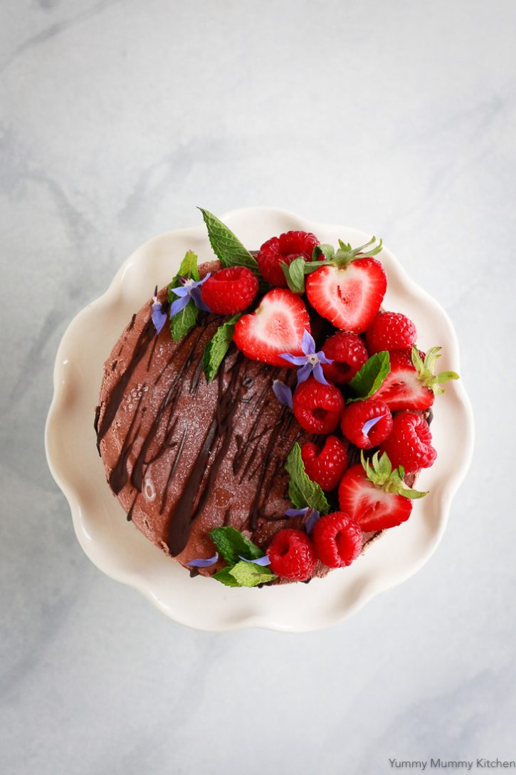 A beautiful vegan chocolate cheesecake drizzled with chocolate and garnished with berries image from above.