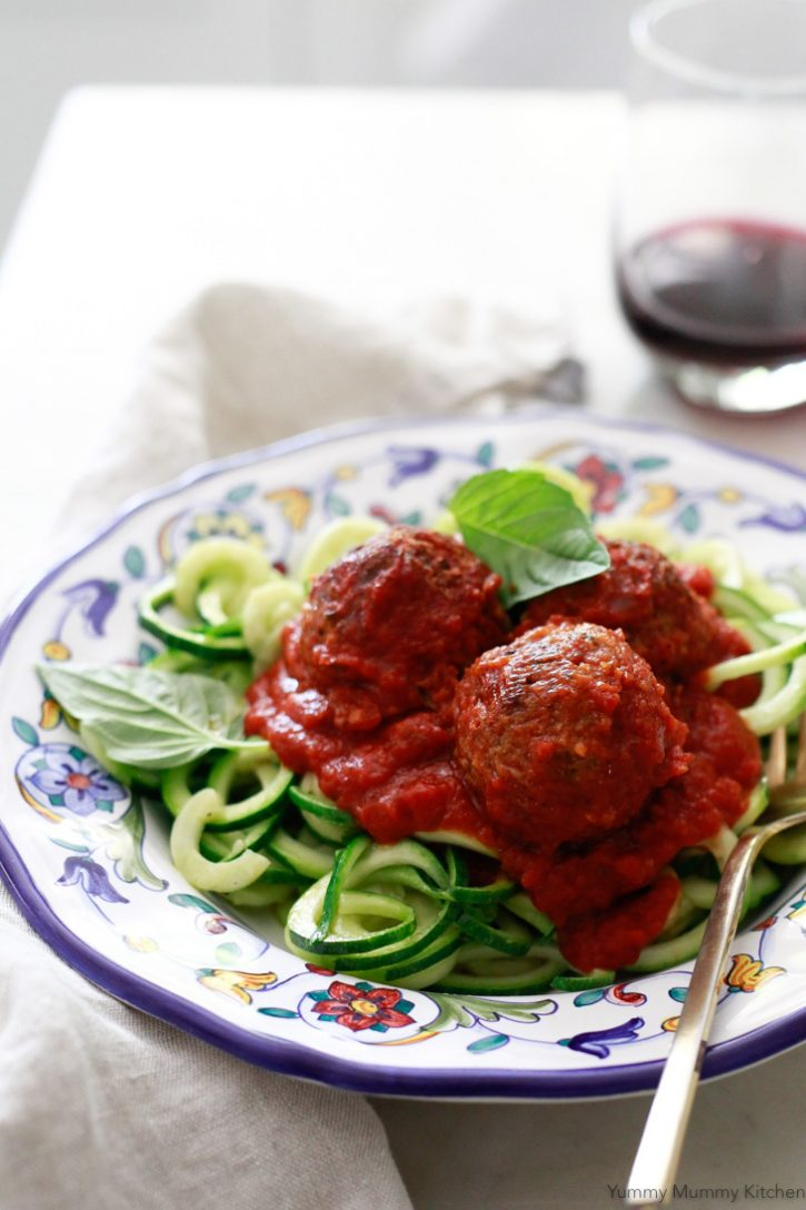 A plate of vegan meatless meatballs with marinara sauce on zucchini noodles.