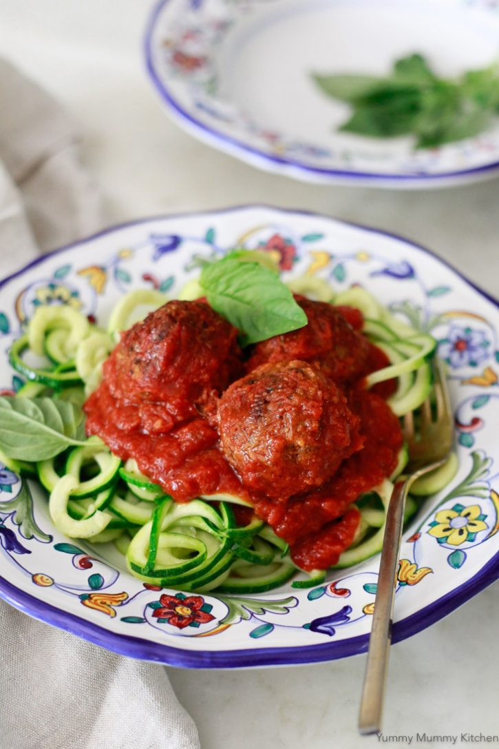 A plate of zucchini noodles with marinara sauce and vegan lentil meatballs.