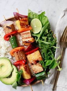 Beautiful grilled vegetable, pineapple, and tofu kabobs on a plate with rice.