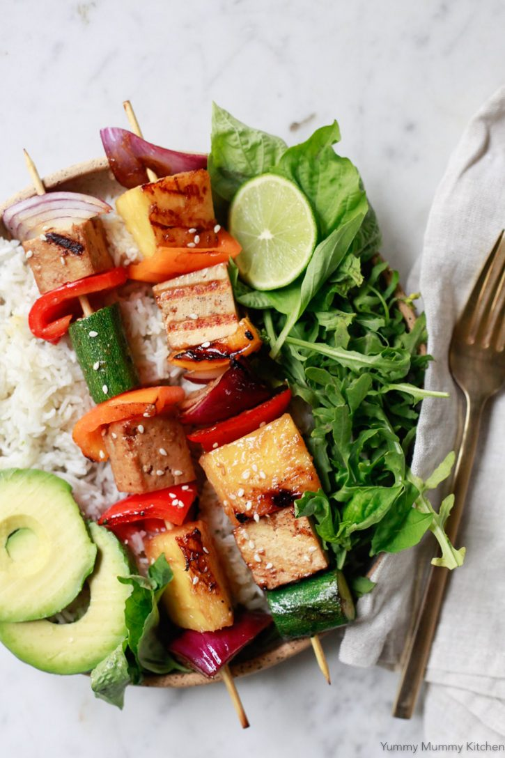 Grilled veggie kabobs with peppers, onions, zucchini, pineapple and teriyaki marinade on bed of rice with avocado and salad. These vegetable kabobs are perfect for a vegetarian or vegan BBQ.