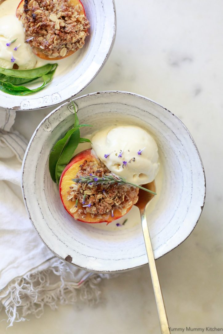 Beautiful miniature peach crisps. Baked peaches topped with a gluten-free vegan oatmeal crumble topping and served with vanilla ice cream. These baked peaches are topped with fresh lavender flowers.