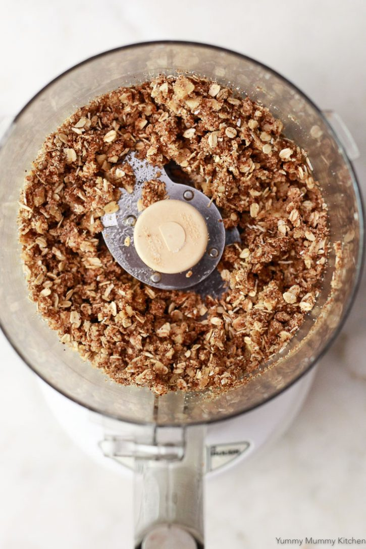 Oatmeal fruit crisp topping in a food processor is ready to top peaches.