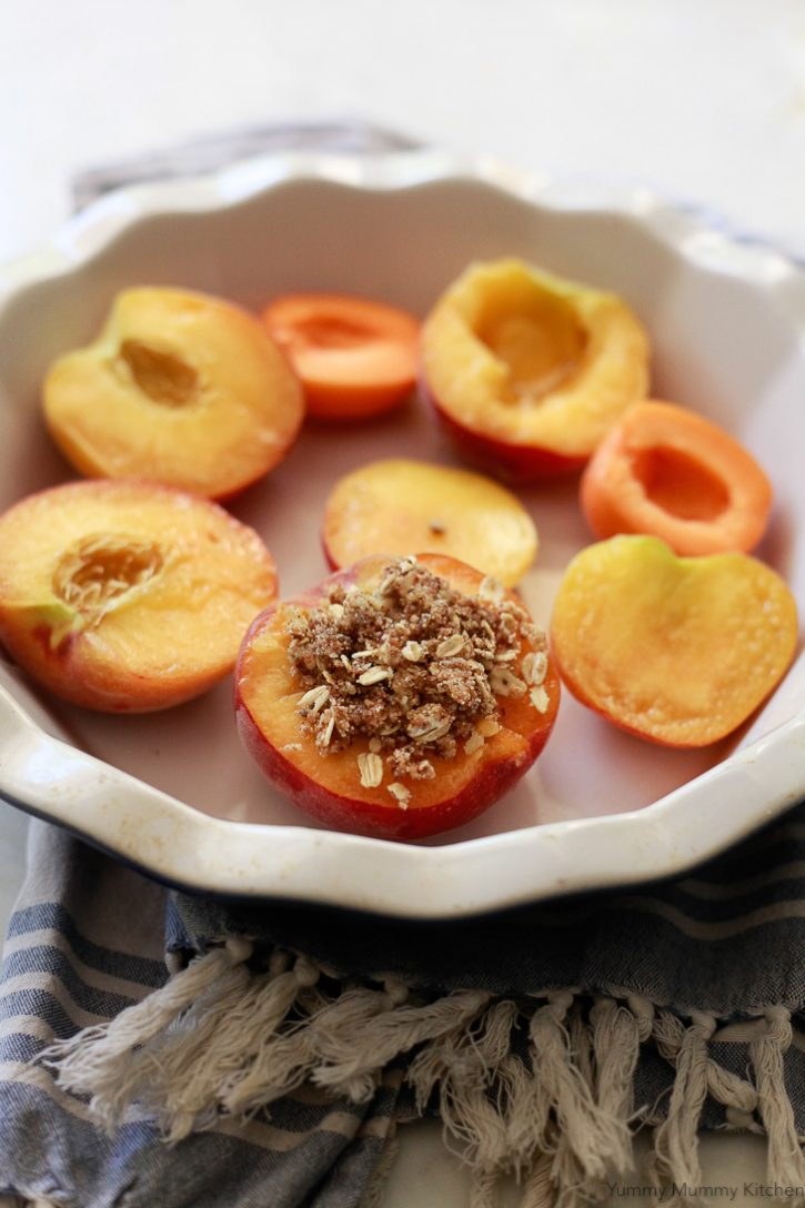 Fresh peaches in a baking dish get topped with a fruit crisp topping of nuts and oats.