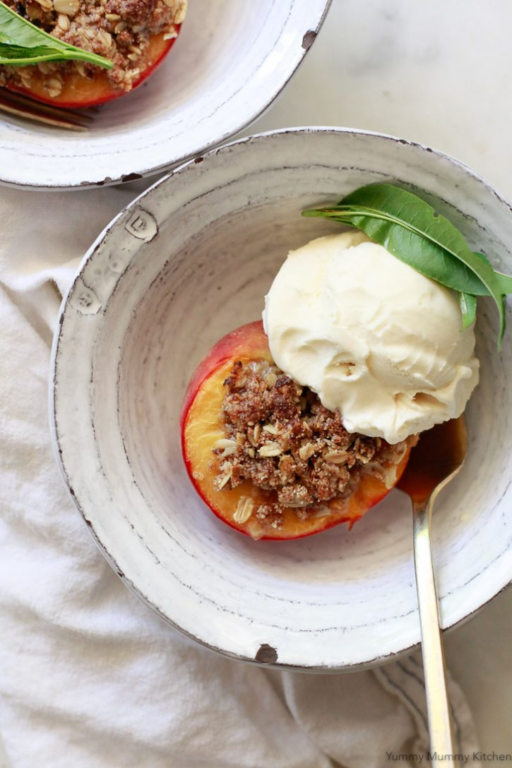 Baked peaches stuffed with oatmeal crisp topping and served with vegan vanilla ice cream. A beautiful summer dessert.