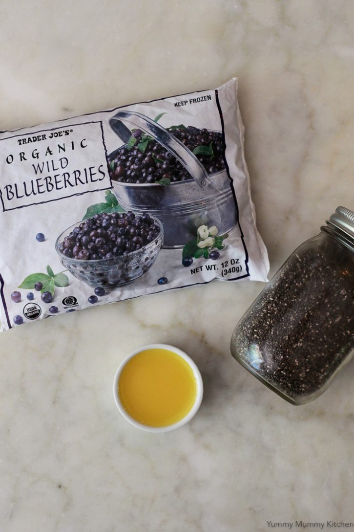 Blueberry chia jam ingredients include a bag of frozen organic blueberries, orange juice, and chia seeds.