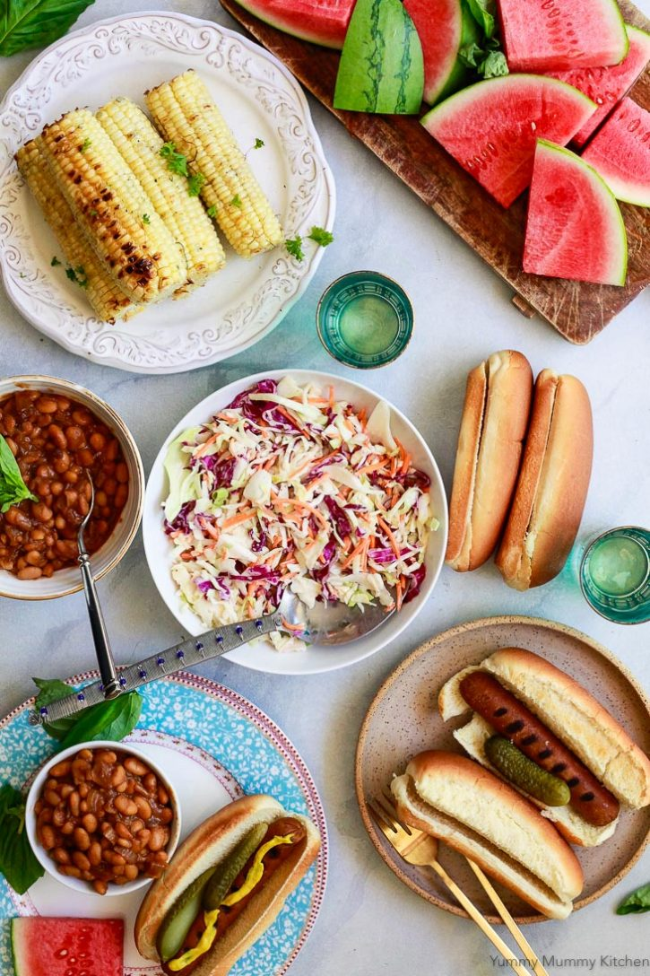 A beautiful vegetarian BBQ spread including veggie hotdogs, grilled corn, vegan coleslaw, watermelon, and baked beans.