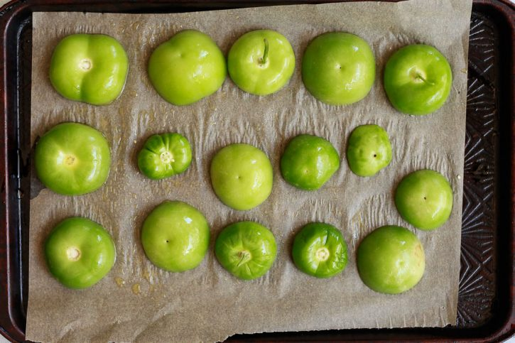 Tomatillo halves on a baking sheet before going into the oven to roast.