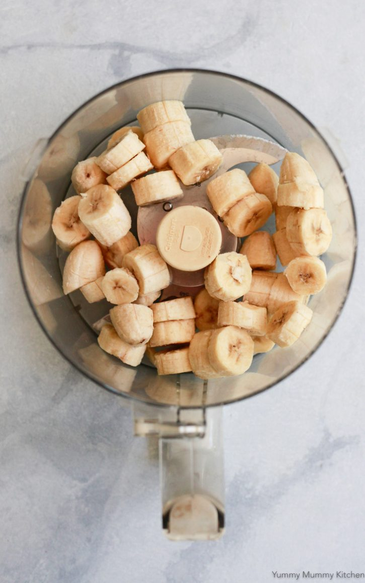 Frozen sliced banana in a food processor are ready to be made into nice cream.