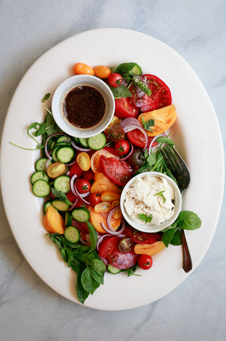 A fresh tomato salad recipe with cucumber, onions, basil, and a simple balsamic vinaigrette is a delicious and easy summer side dish.