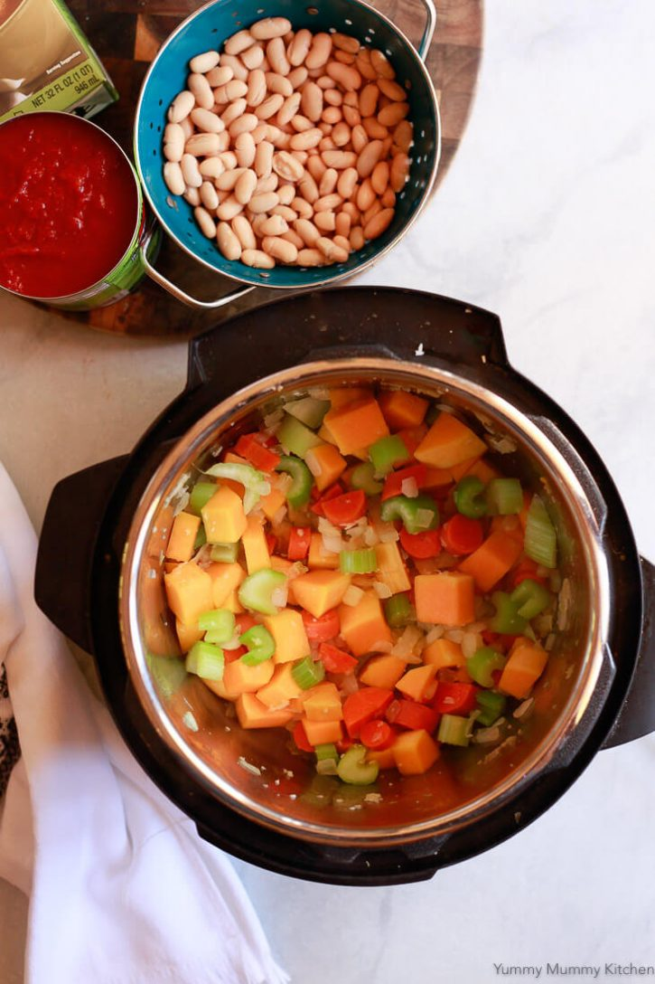 Onion, butternut squash, carrots, and celery are sauteed in an Instant Pot before getting pressure cooked with beans, tomatoes, pasta and broth in this easy minestrone recipe.