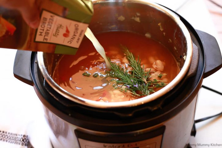 Vegetable broth gets added to the Instant Pot before pressure cooking an easy minestrone soup recipe.