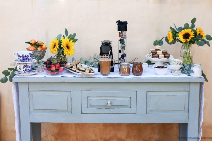 A coffee and dessert bar set on an antique table for a party.
