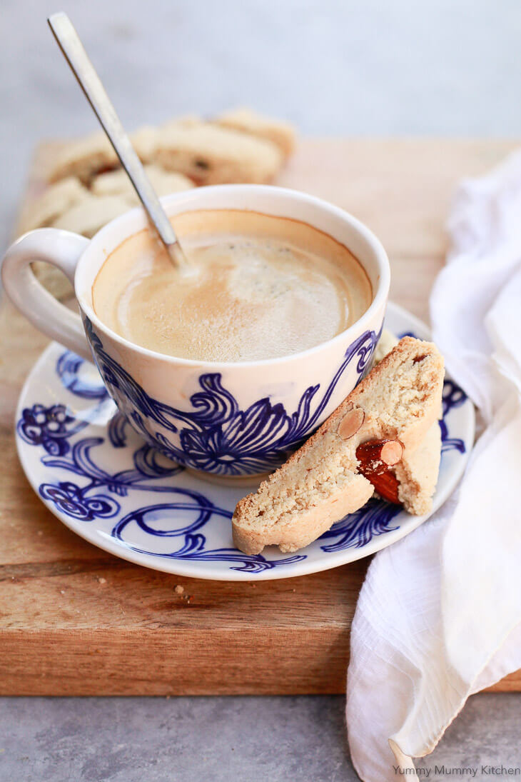 Gluten free almond cantucci biscotti on a plate with a cup of coffee.