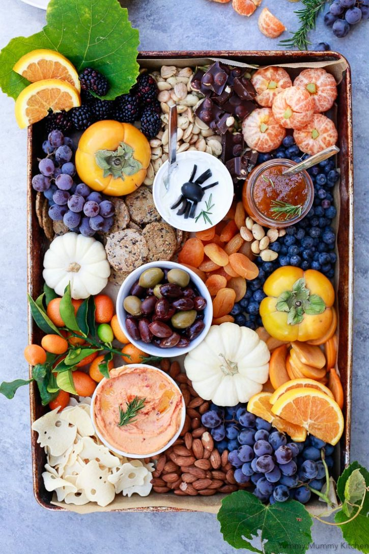 A beautiful Halloween inspired party platter filled with healthier orange and black ingredients. From grapes to olives, red pepper hummus, and tangerine pumpkins, this party board is perfect for any Halloween Party.