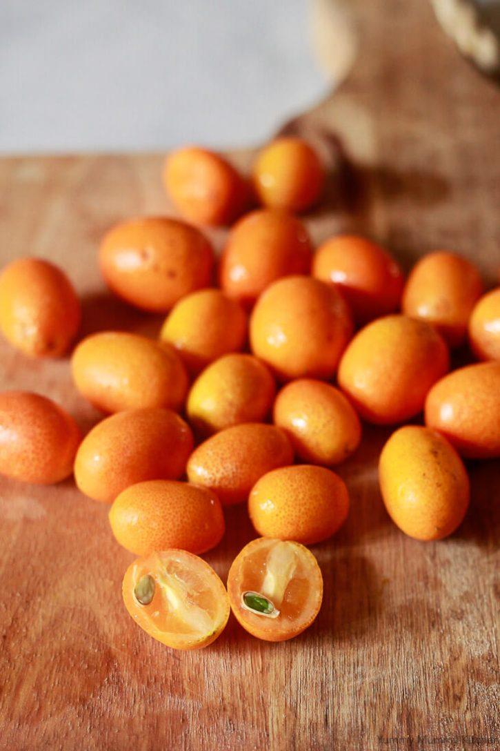 A kumquat is cut in half to prepare for kumquat marmalade. A kumquat seed is shown inside the fruit.